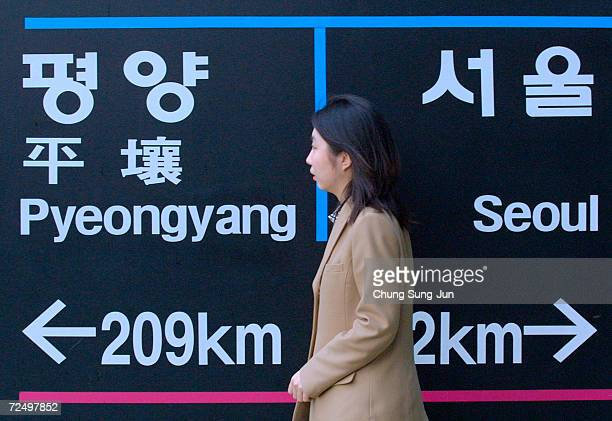 An unidentified South Korean woman walks past a signpost showing directions to the North Korean capital at Imjinkak station and to Seoul in South...