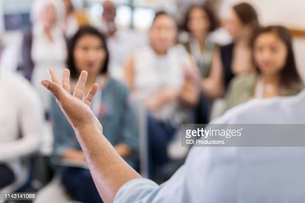 an unidentified speaker explains his point - town hall stock pictures, royalty-free photos & images
