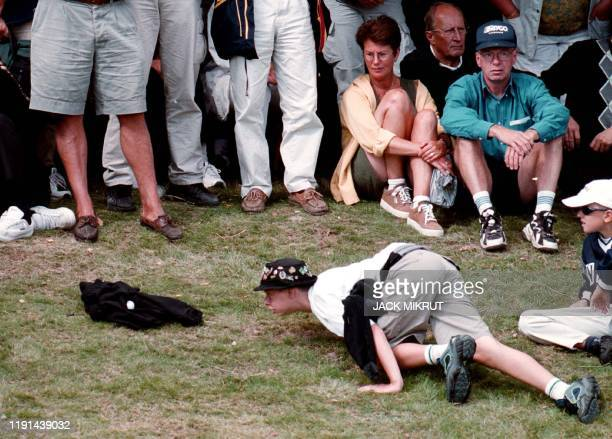 An unidentified spectator checks out the golf ball of Britain's Laura Davies after it landed on a jersey someone in the audience had put on the...