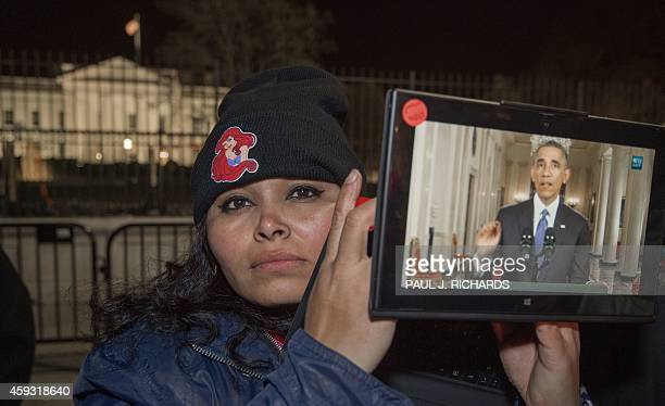 An unidentified supporter stands in front of the White House and holds an iPad streaming the live address to the nation by US President Barack Obama...