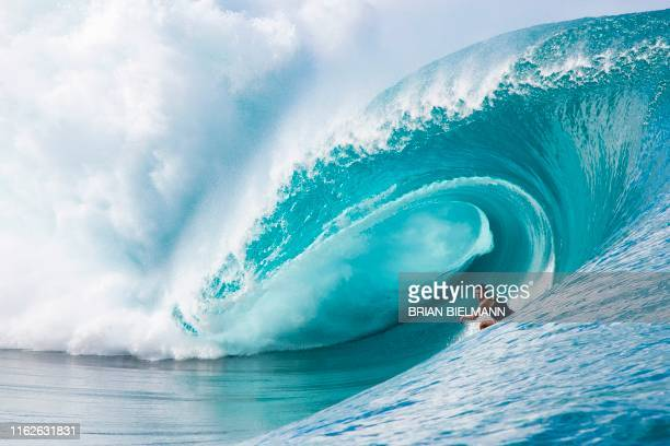 TOPSHOT An unidentified surfer practices ahead of the WSL Tahiti pro surfing trial at the famous break Teahupoo in Tahiti French Polynesia on August...