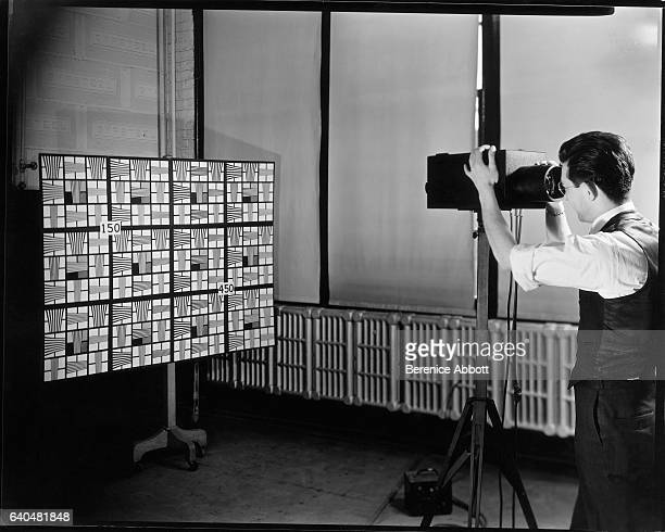 An unidentified television engineer uses an electronic telescope to measure image distortion with a pattern board Camden New Jersey late 1950s...
