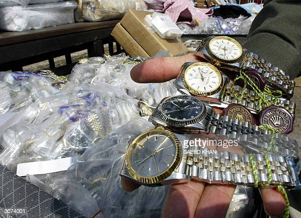 An unidentified Thai customs officer shows counterfeit Rolex watches confiscated in different raids during a display at the customs house in Bangkok...