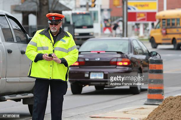An unidentified Toronto Police officer works paid duty at the corner of Woodbine and Kingston Rd April 30 2015 Mayor John Tory talks about...