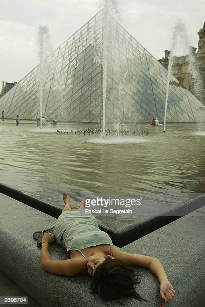 An unidentified tourist cools off in the fountain of the Pyramide du Louvre August 13 2003 in Paris The heat has hovered in the mid30s Celsius in...