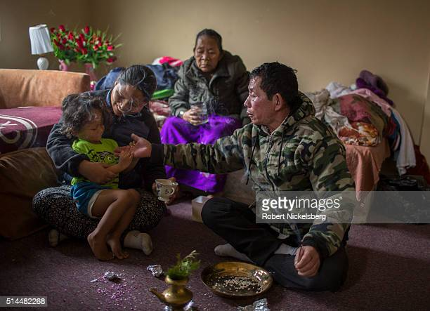 An unidentified traditional Buddhist healer holds out his hand to Dipson Gurung who sits in the lap of his mother Hema in their family's living room...