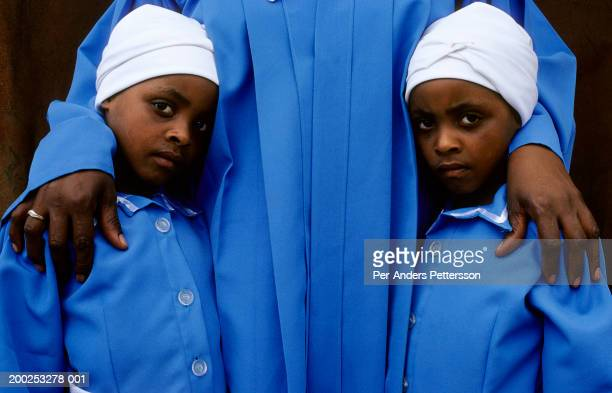 An unidentified twin girls attends an early morning church service with members of the Zion church on July 15, 2001 in Site B Khayelitsha, a township...