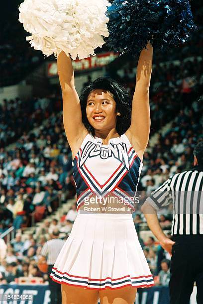 An unidentified University of Connecticut cheerleader raises her pom-poms to stir up the crowd, Hartford Connecticut, 1994.