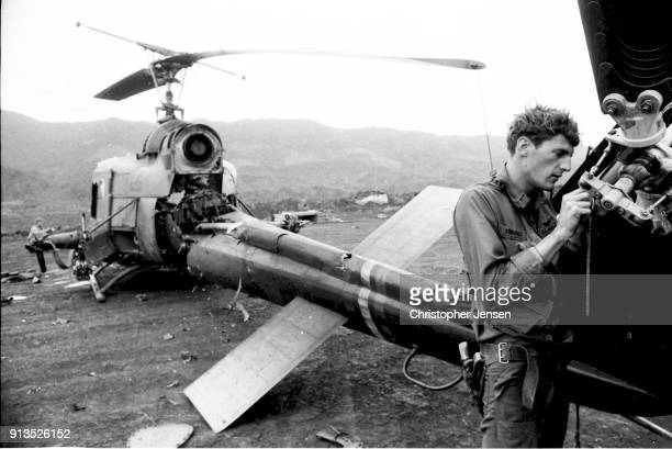 An unidentified US Air Force pilot salvages part of the tail rotor from his destroyed Bell UH1 Iroquois helicopter better known as a Huey Khe Sanh...