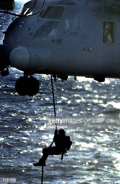 An unidentified US Navy SEAL rappels from a MH53 'Pave Low' helicopter to the deck of the amphibious command ship USS Mount Whitney during a training...