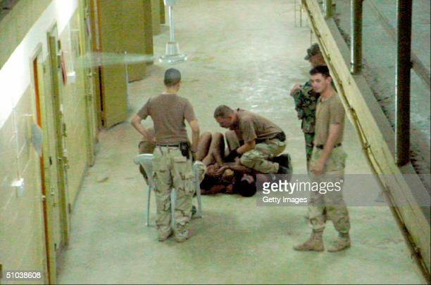 An unidentified US soldier at Abu Ghraib prison appears to be kneeling on naked detainees at the Abu Ghraib prison in these undated still photos...