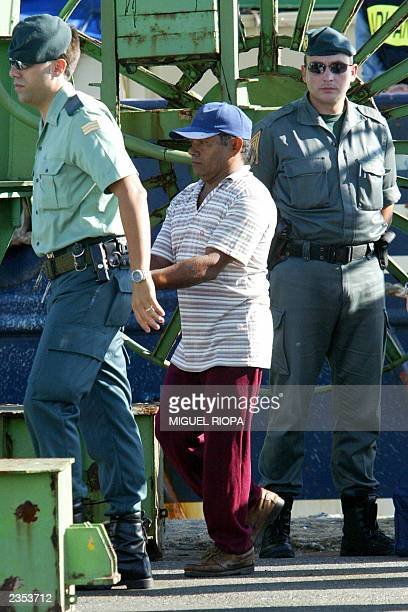 "An unidentified Venezuelan citizen is led handcuffed by a Spanish Civil Guard after the arrival of the seized ""Poseidon"" vessel at Vilagarcia de..."