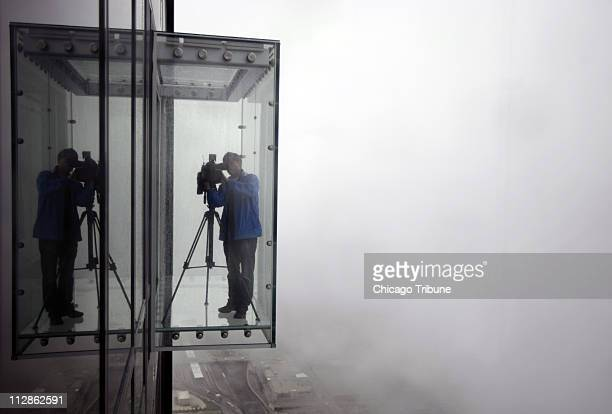 An unidentified videographer from a local Chicago television station shoots from 'The Ledge' a new addition to the Sears Tower in Chicago Illinois...