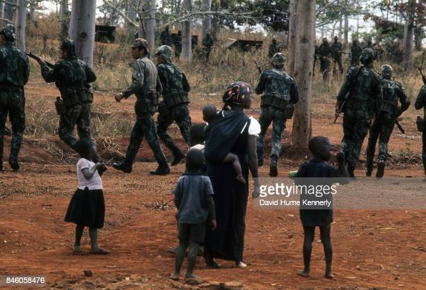 An unidentified woman and group of children watch as Colonial Portuguese soldiers train in the woods Ancuabe Cabo Delgado Province Mozambique July 27...