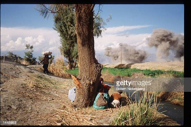An unidentified woman and her child sits near a tree while the government bombs the area March 15 1989 in Jalalabad Afghanistan The end of Soviet...