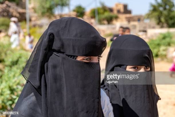 an unidentified woman and her daughters in traditional dresses walk hand in hand in the sanaa street. - niqab stock pictures, royalty-free photos & images