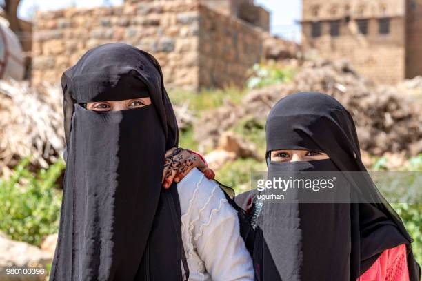 an unidentified woman and her daughters in traditional dresses walk hand in hand in the sanaa street. - nikab stock pictures, royalty-free photos & images