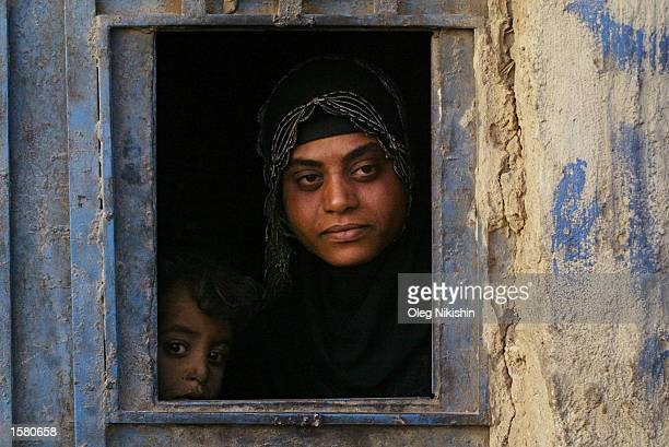An unidentified woman and her son look out from their window onto a street October 29 2002 in the town of Nahawan which is located approximately 37...