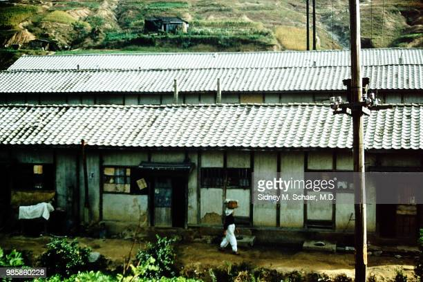 An unidentified woman carries a basket on her head as she walks past a hillside home Inchon South Korea September 1952