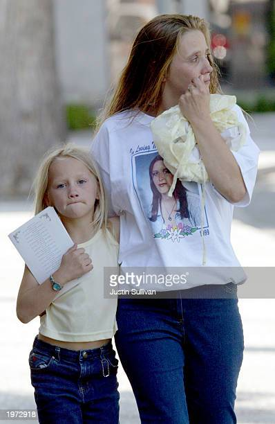 An unidentified woman cries as she and a young girl leave a memorial service for Laci Peterson and her unborn son Connor May 4 2003 in Modesto...