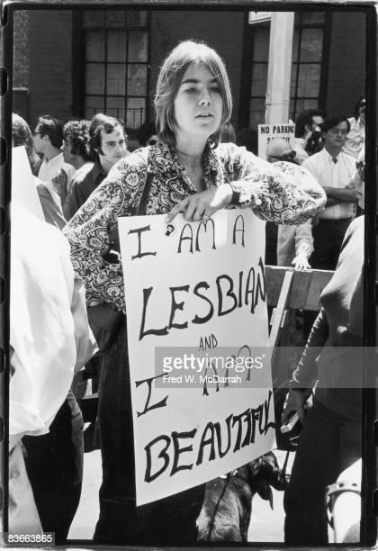 An unidentified woman holds a large sign that reads 'I am a lesbian and I am beautiful' during the first Stonewall anniversary march then known as...