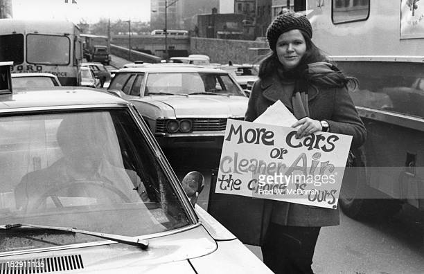 An unidentified woman holds a sign that reads 'More Cars or Cleaner Air the Choice is Ours' near the entrance to the Midtown Tunnel New York New York...