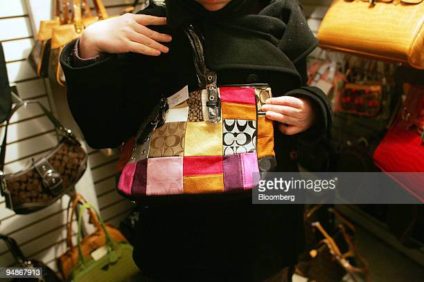 An unidentified woman holds up a counterfeit Coach handbag in the back room of tourist shop in New York City's Chinatown on Wednesday, February 1,...