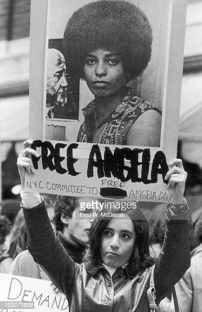 An unidentified woman holds up a poster that reads 'Free Angela' and features a large photograph of imprisoned American political activist and...