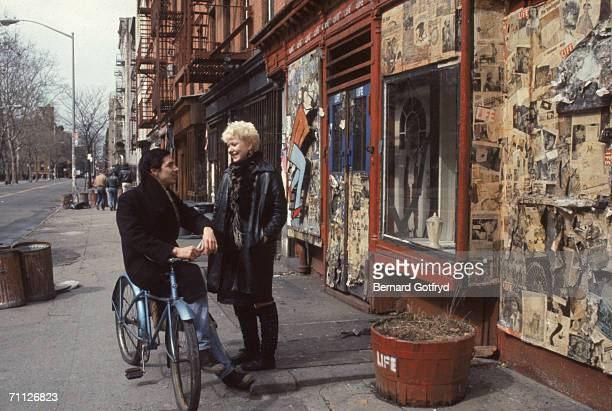An unidentified woman in a leather jacket stands on a sidewalk and talks with a man as he leans on a blue bicycle in the East Village neighborhood of...