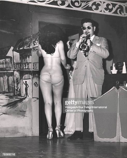 An unidentified woman in a transparent bikini and high heels leaves the stage to the music of a trumpeter after her striptease routine late 1940s...