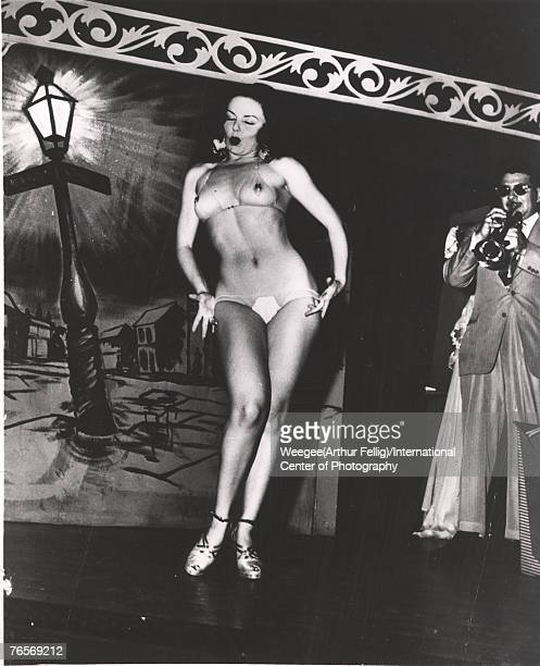 An unidentified woman in a transparent bikini and high heels purses her lips as she performs a striptease dance to the music of a trumpeter on stage...