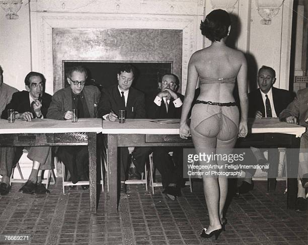 An unidentified woman in transparent undergarments stands before a table of male judges at a beauty contest 1940s or 1950s Photo by...