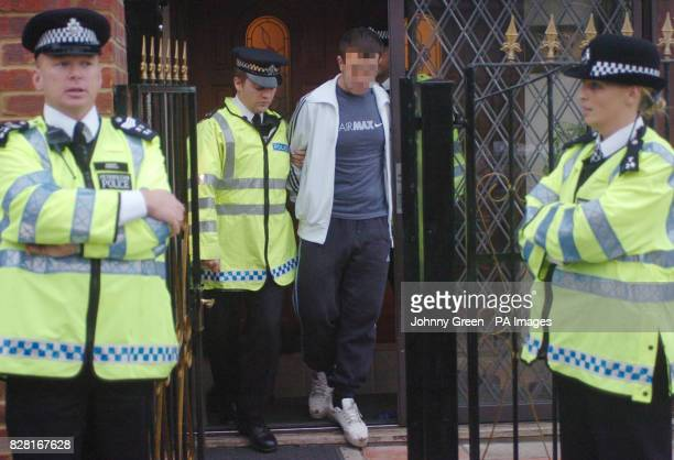 An unidentified woman is led out of an address by police in Welling southeast London Tuesday October 11 2005 Five men including former asylum seekers...