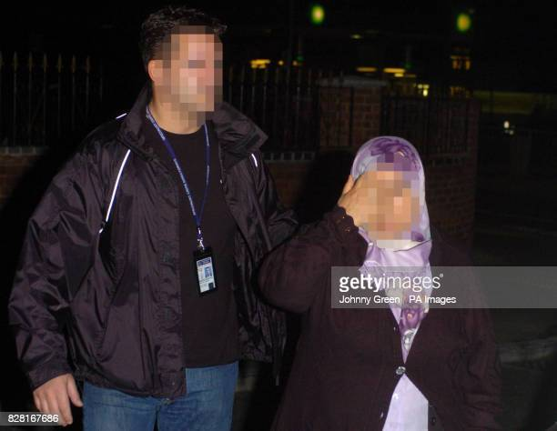 An unidentified woman is led out of an address by police in Welling southeast London Tuesday October 11 2005 during raids to smash a multimillion...