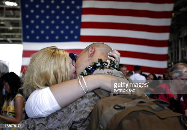 An unidentified woman kisses her fiance, a US marine with 1/3 Marines Bravo Company, upon his return to Hawaii on June 13 following a seven- month...