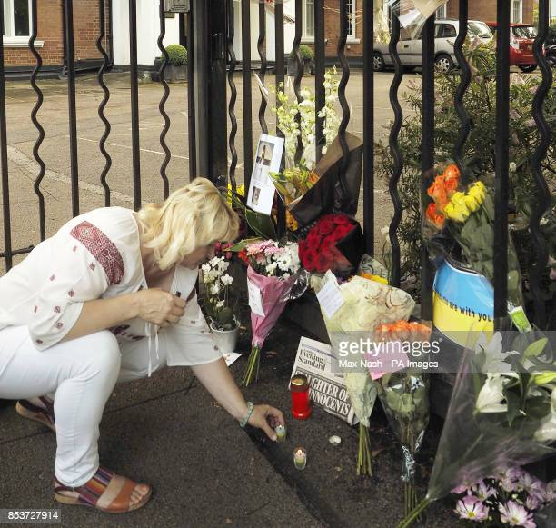 An unidentified woman lights a candle at a shrine outside the Netherlands Embassy in London for the victims in the Malaysian airlines crash