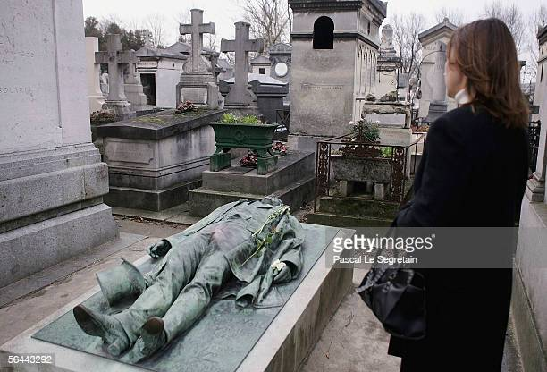 An unidentified woman looks at Victor Noir's grave in the Pere Lachaise Cemetery on December 16 2005 in Paris France Folklore surrounding a well...
