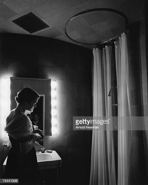 An unidentified woman looks in her purse as she stands in the bathroom of the Glass House New Canaan Connecticut July 1 1949 The photographer is...