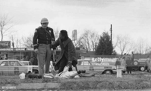 An unidentified woman moves to block a uniformed police officer as they both stand over the unconscious body of Civil Rights activist Amelia Boynton...