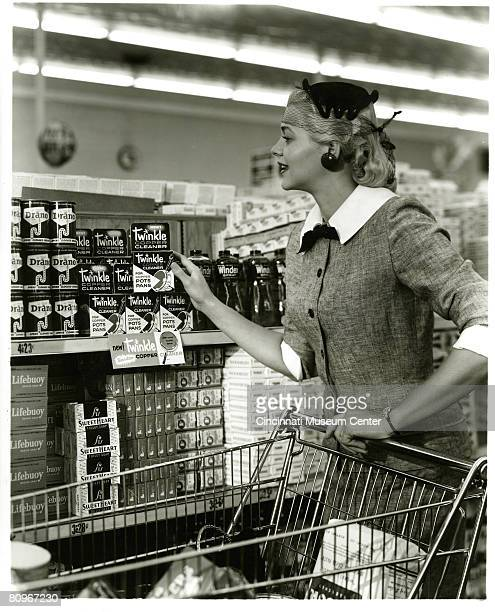 An unidentified woman picks up a box of Twinklebrand copper cleaner as shepushes a shopping cart along the aisle of a supermarket late 1950s Other...