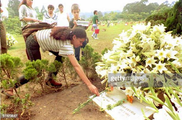 An unidentified woman places flowers on the grave of slained Medellin drug cartel boss Pablo Escobar 30 Nov at a local cemetery in Medellin. Escobar...