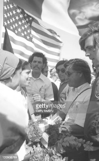 An unidentified woman presents flowers to American labor activist Cesar Chavez while on the United Farm Worker's 1000 Mile March near King City...