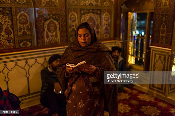 An unidentified woman reads from a copy of Sikh holy scriptures in the Harmandir Sahib Amritsar India February 23 2014 The Temple sees an estimated...