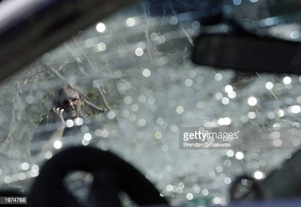 An unidentified woman seen through a smashed windshield which was damaged in a recent tornado talks on a cell phone May 5 2003 in Gladstone Missouri...