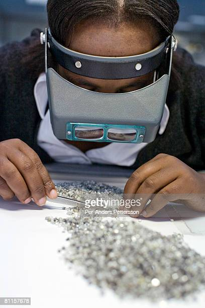 An unidentified woman sorts raw diamonds as they are displayed on tables at the new Diamond Trading Company the world's largest and most advanced...