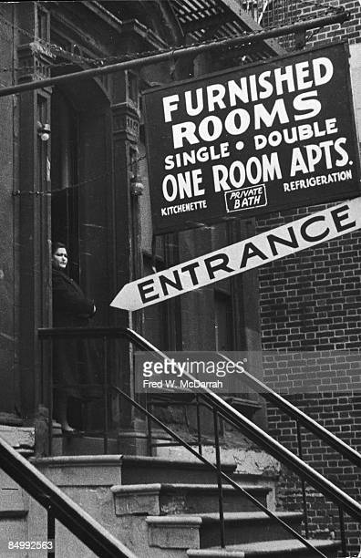 An unidentified woman stands on the stoop of a building next door to one which advertises 'Furnished Rooms' mid to late 20th century