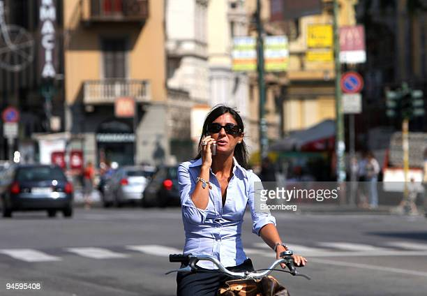 An unidentified woman uses her cell phone while on a bicycle in Milan, Italy, Saturday, September 9, 2006. Telecom Italia SpA, Italy's biggest phone...