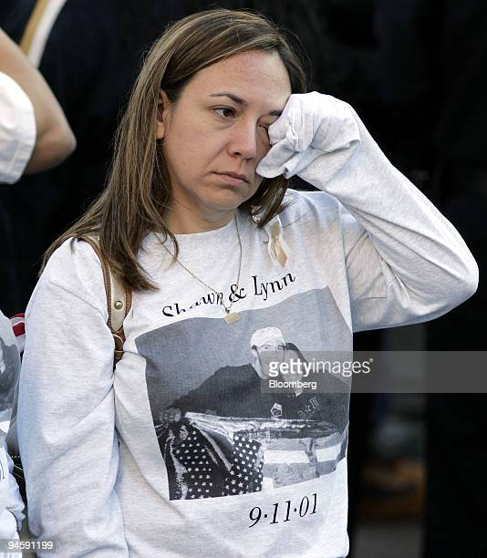 An unidentified woman wipes her eye while waiting for the start of the memorial service at the site of the former at the World Trade Center Monday...