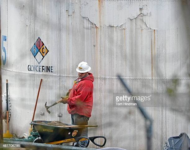 An unidentified worker at Freedom Industries shovels NAPA premium oil absorbent on January 10 2014 in Charleston West Virginia West Virginia American...