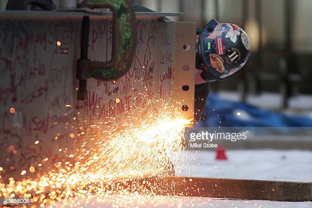An unidentified worker prepares the steel beam that will be raised to the highest structual point in the Prudential Center's construction site during...